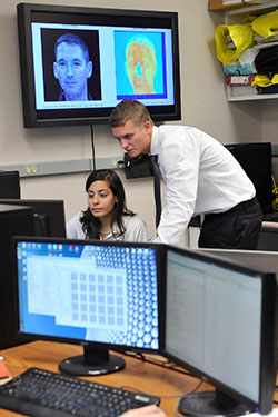 photo of two students looking at a monitor