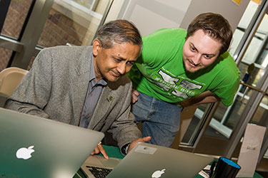 photo of a student and professor looking at a laptop