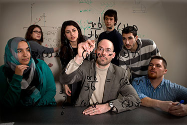photo of the dean and students working on an equation