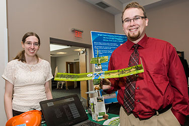 photo of two students with their design at the showcase