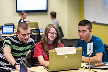 photo of students looking at a laptop