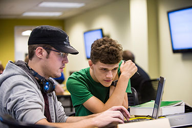 photo of two students looking at a laptop