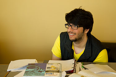 photo of a student sitting at a desk with books