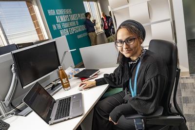 Student sits at a computer at Booz Allen Hamilton